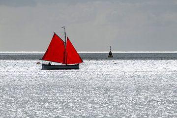 Zeilbootje met rood zeil tegen de schittering van de zon op de Waddenzee nabij het eiland Terschelli van Tonko Oosterink