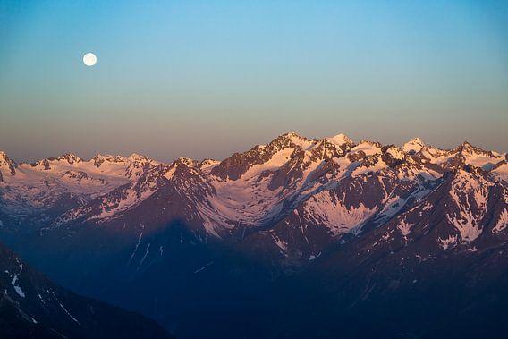 Zonsondergang over besneeuwde bergtoppen in de alpen