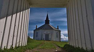Zicht door de poort van de witte kerk van Dverberg, Noorwegen vanuit het kikkerperspectief