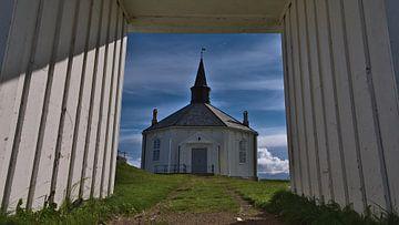 Zicht door de poort van de witte kerk van Dverberg, Noorwegen vanuit het kikkerperspectief van Timon Schneider