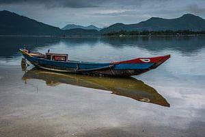 Vissersboot met reflectie in het water. van