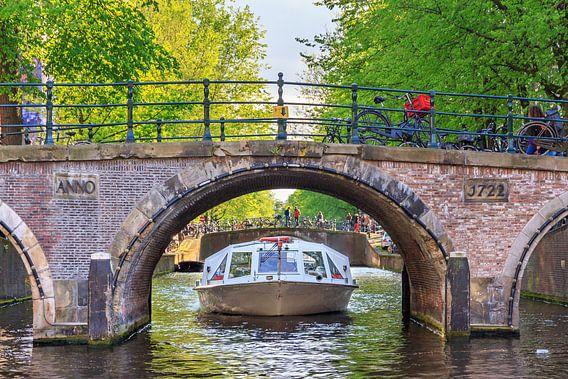 Rondvaart onder de brug in Amsterdam van Dennis van de Water