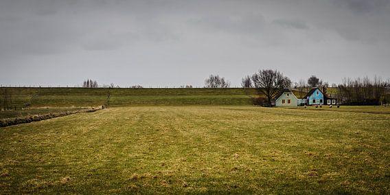 Landschap met dijk, dijkhuizen, grasland en dreigende lucht
