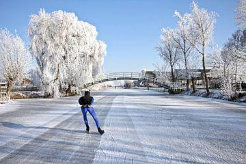 Eenzame schaatser op bevroren sloot op het platteland in Nederland van Nisangha Masselink