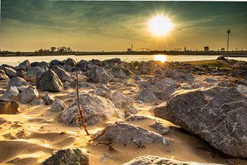 Sonnenuntergang an der Waal bei Nimwegen mit den Felsen des Flusses am Ufer. von Rianne Groenveld