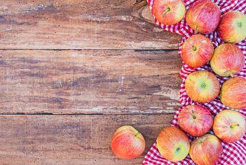 Vele rode appelen op rustieke houten lijst bovenaanzicht met rood geruit tafelkleed en exemplaarruim van Alex Winter