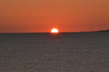 zonsondergang aan de kust van Denemarken met een wolkeloze hemel van tiny brok