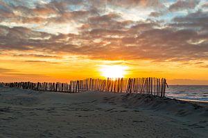 Hekwerk aan de kust met zonsondergang