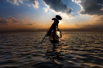 Visser die met traditionele boot op het Inle meer in Myanmar op ouderwetse wijze met een vis korf vi van
