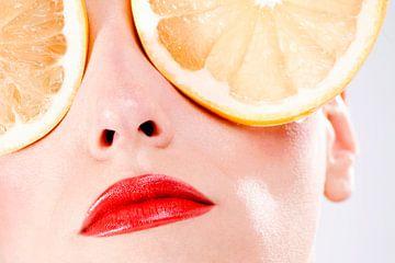 SF00989776 Visage de femme aux yeux couverts de tranches d'orange sur BeeldigBeeld Food & Lifestyle