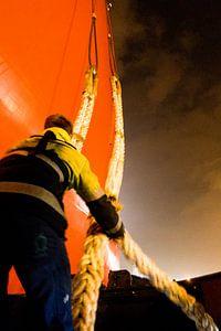 Havenwerker vangt trossen op om een schip aan te meren van