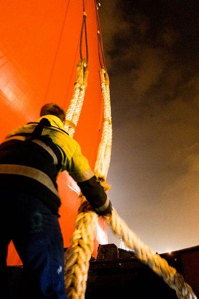 Havenwerker vangt trossen op om een schip aan te meren