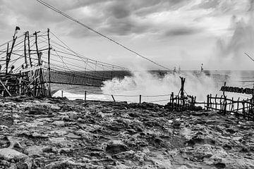 Une grande vague rencontre une passerelle en corde balançoire reliée à une île rocheuse. sur kall3bu