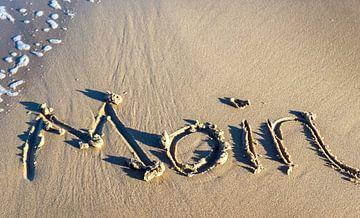 Noord-Duitse groet Moin geschreven in het strandzand aan de Oostzee