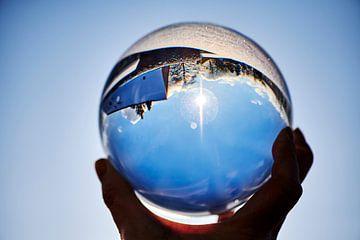Kijkend door een kristallen bol naar een winterlandschap. van Michaela Bechinie