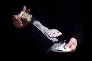 twee handen shuffle vallende kaarten met bewegingsonscherpte tegen een zwarte achtergrond, zakelijke