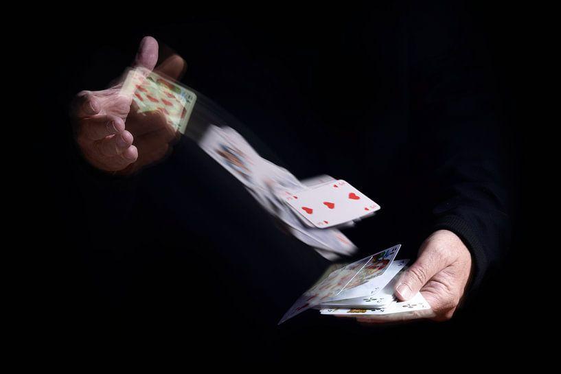 twee handen shuffle vallende kaarten met bewegingsonscherpte tegen een zwarte achtergrond, zakelijke van Maren Winter