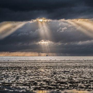 Rayons de lumière au-dessus de la mer des Wadden, vus de Harlingen au coucher du soleil.