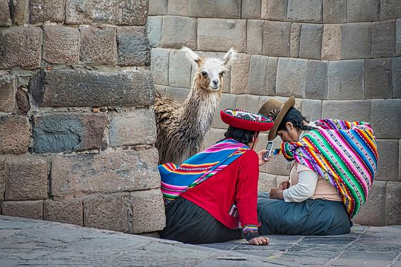 Twee Peruaanse vrouwen met lama bij een oude Incamuur