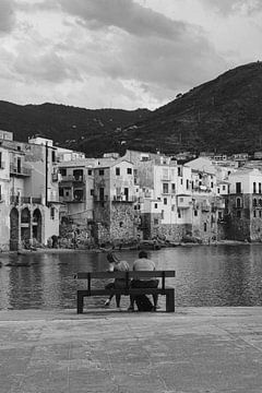 Koppel aan het water met uitzicht op de stad van Cefalu, Sicilië Italië in zwartwit van Manon Visser