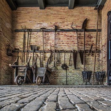 Tuingereedschap tegen een oude muur van