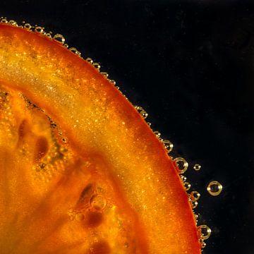 Schijfje tomaat in water met bubbels