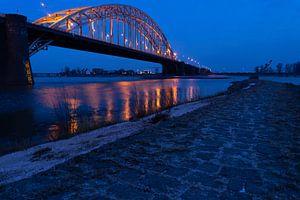Brücke über den Fluss Waal nach Lent van Nijmegen in der Morgendämmerung mit dunkelblauem Himmel und von Leoniek van der Vliet