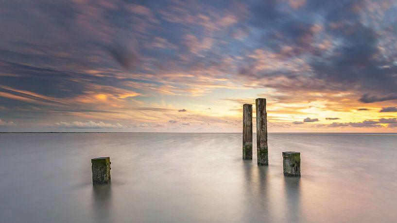 Palen in de waddenzee tijdens zonsondergang van Martijn van Dellen