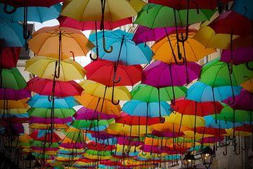Gekleurde paraplu's in een straat van Patrick Verhoef