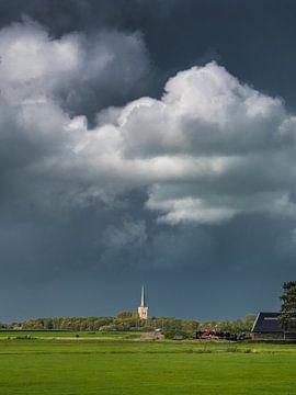 Der Kirchturm von Tzum im Sonnenlicht mit einem bedrohlichen Himmel von Harrie Muis