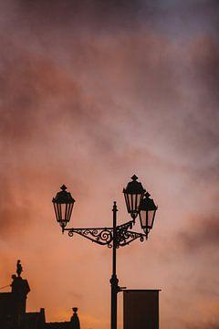 Silhouet van een lantaarnpaal in Delft tijdens zonsondergang van Robin van Steen