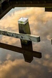 Meerpaal in een weerspiegeling van de wolken lucht in het water. One2expose Wout Kok Photography van