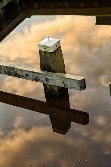 Meerpaal in een weerspiegeling van de wolken lucht in het water. One2expose Wout Kok Photography van Wout Kok