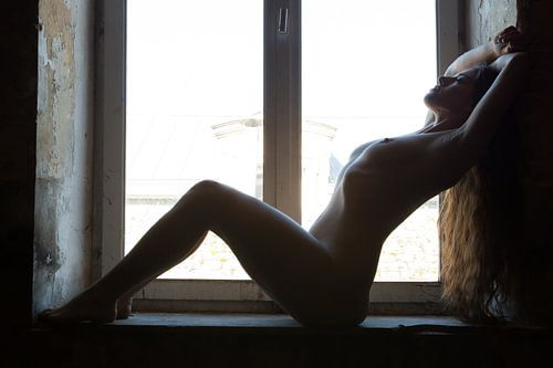 Artistiek naakt vrouw in zittende pose bij het raam