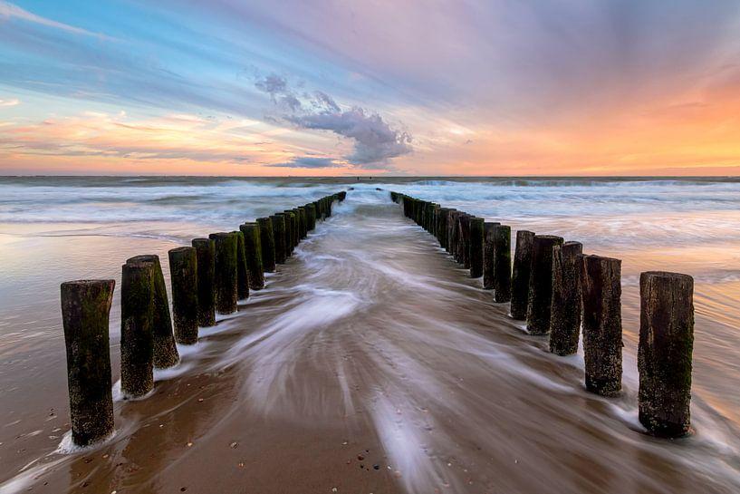 Golfbrekers op het strand tijdens een stormachtige zonsondergang van Arnoud van de Weerd