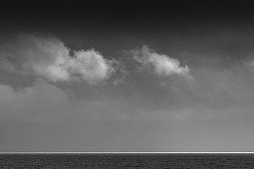 Weiße Wolken über dem Wattenmeer mit einem weißen Lichtstreifen am Horizont in Schwarz-Weiß. von Tonko Oosterink