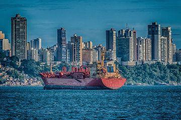 Vrachtschip verankerd in de baai van Allerheiligen met de skyline van de stad Salvador, Brazilië van Castro Sanderson
