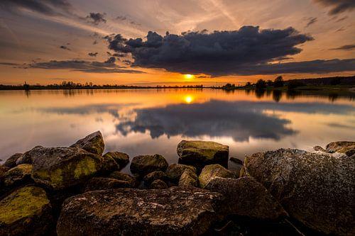 Als de zon bijna achter wolken verdwijnt tijdens de zonsondergang