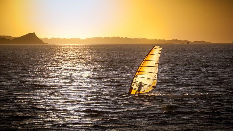 Surfer nog net even tijdens de zonsondergang van Karel Pops