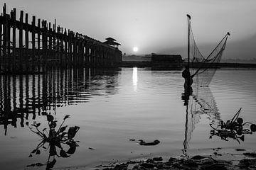 Der Fischer hält sein Fischernetz neben der U-Bein-Brücke in Myanmar hoch. von Twan Bankers