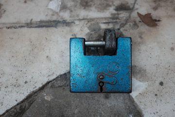 Blauw hangslot op verweerd marmer  van Marc Wielaert