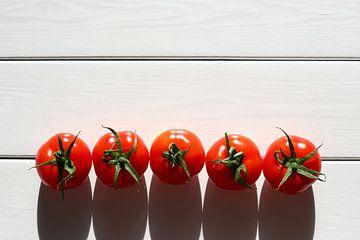 Vijf tomaten op een rij in de zon op een houten tafel van Maarten Pietersma