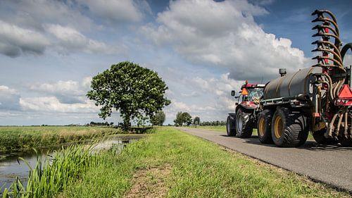 De boer aan het werk met zijn tractor van