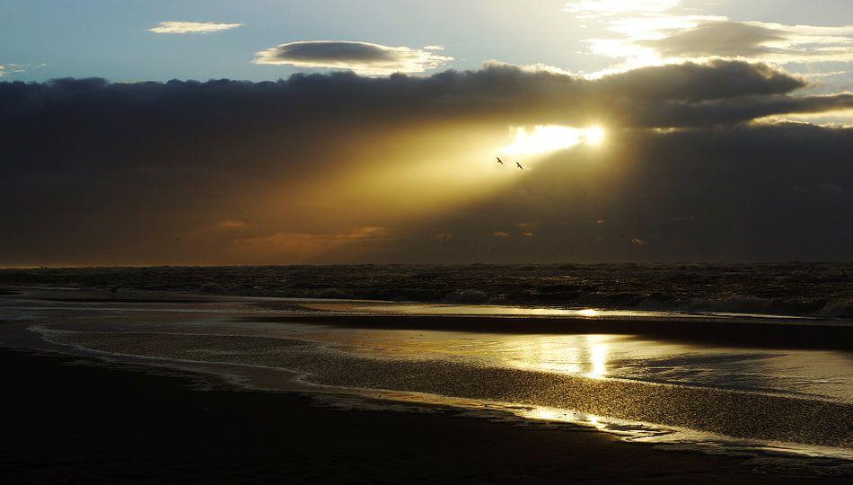 zonnestraal door de wolken boven zee