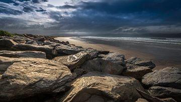 Rotsblokken aan Iers strand onder dreigende wolken van Michel Seelen