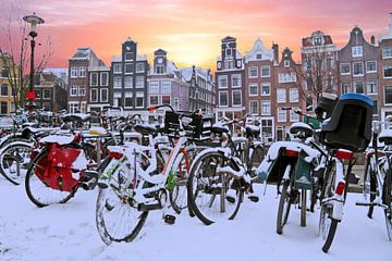 Besneeuwde fietsen in Amsterdam Nederland bij zonsondergang van