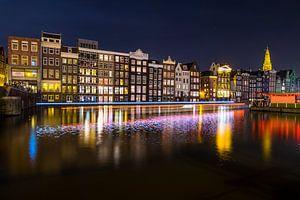 Damrak in Amsterdam met kleurrijke lichtstrepen van een passerende rondvaartboot op het water