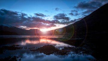 der letzte Sonnenstrahl des Tages über dem windstillen See in Schottland von Studio de Waay