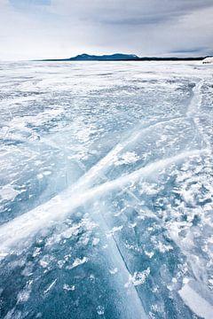 Gekruiste scheuren van doorzichtig ijs op het Baikalmeer, bergen in de verte, harde hemel van Michael Semenov