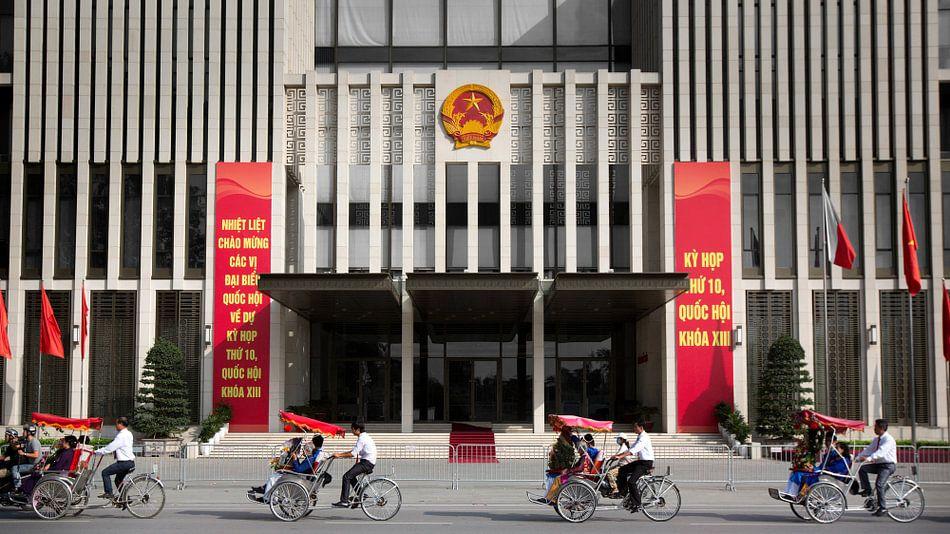 Rickshaw procession passing by parliament building in Hanoi, Vietnam van Fleur Halkema